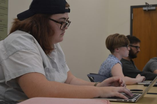 Aeolus editor and second-year Hope Sparks and Bethany Wilson, along with third- year Jace Johnson are seen working on the journal during one of their meetings.