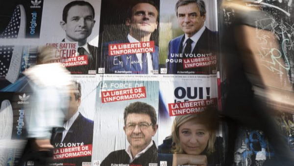 A pedestrian passes by posters by NGO group 'Reporters Without Borders' depicting six of the French presidential election candidates, including (clockewise from top left) Benoit Hamon, Emmanuel Macron, Francois Fillon, Marine Le Pen, Jen-Luc Melenchon, in Paris. [Ian Langsdon/EPA]