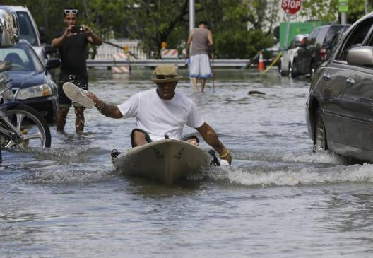 Photo courtesy of Lynne Sladky/Associated Press Juan Carlos Sanchez paddled a kayak with his shoes on a flooded street in Miami Beach last year.